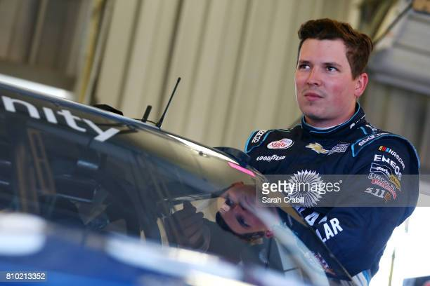 Brennan Poole driver of the DC Solar Chevrolet stands in the garage during practice for the NASCAR XFINITY Series Alsco 300 at Kentucky Speedway on...