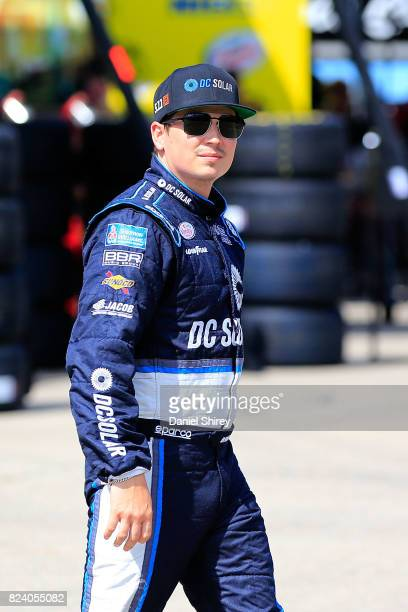 Brennan Poole driver of the DC Solar Chevrolet walks through the garage area during practice for the NASCAR XFINITY Series US Cellular 250 Presented...