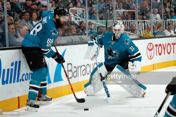 Brent Burns and Martin Jones of the San Jose Sharks tend to the puck behind the net during a NHL game against the Vancouver Canucks at SAP Center at...