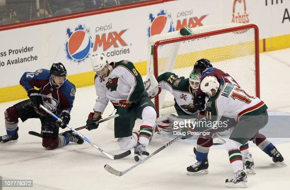 Brent Burns of the Minnesota Wild gets his foot on the puck as he helps goalie Niklas Backstrom defends the goal against Kevin Porter of the Colorado...