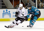 Brent Burns of the San Jose Sharks and Anze Kopitar of the Los Angeles Kings go for the puck during their preseason game at SAP Center on September...