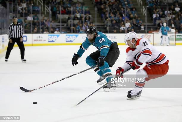 Brent Burns of the San Jose Sharks and Elias Lindholm of the Carolina Hurricanes go for the puck at SAP Center on December 7 2017 in San Jose...