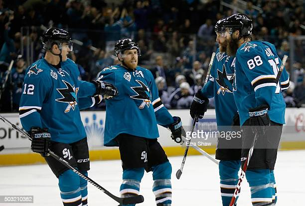 Brent Burns of the San Jose Sharks is congratulated by Patrick Marleau Joe Pavelski and Joe Thornton after he scored a goal against the Winnipeg Jets...