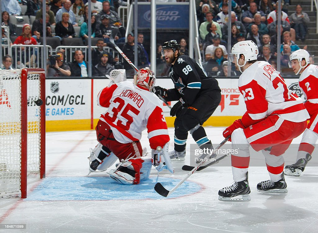 <a gi-track='captionPersonalityLinkClicked' href=/galleries/search?phrase=Brent+Burns&family=editorial&specificpeople=212883 ng-click='$event.stopPropagation()'>Brent Burns</a> #88 of the San Jose Sharks scores a goal against <a gi-track='captionPersonalityLinkClicked' href=/galleries/search?phrase=Jimmy+Howard&family=editorial&specificpeople=2118637 ng-click='$event.stopPropagation()'>Jimmy Howard</a> #35 and Brian Lashoff #23 of the Detroit Red Wings during an NHL game on March 28, 2013 at HP Pavilion in San Jose, California.