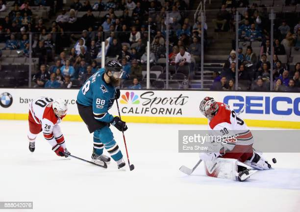 Brent Burns of the San Jose Sharks scores the gamewinning goal on Cam Ward of the Carolina Hurricanes in overtime at SAP Center on December 7 2017 in...
