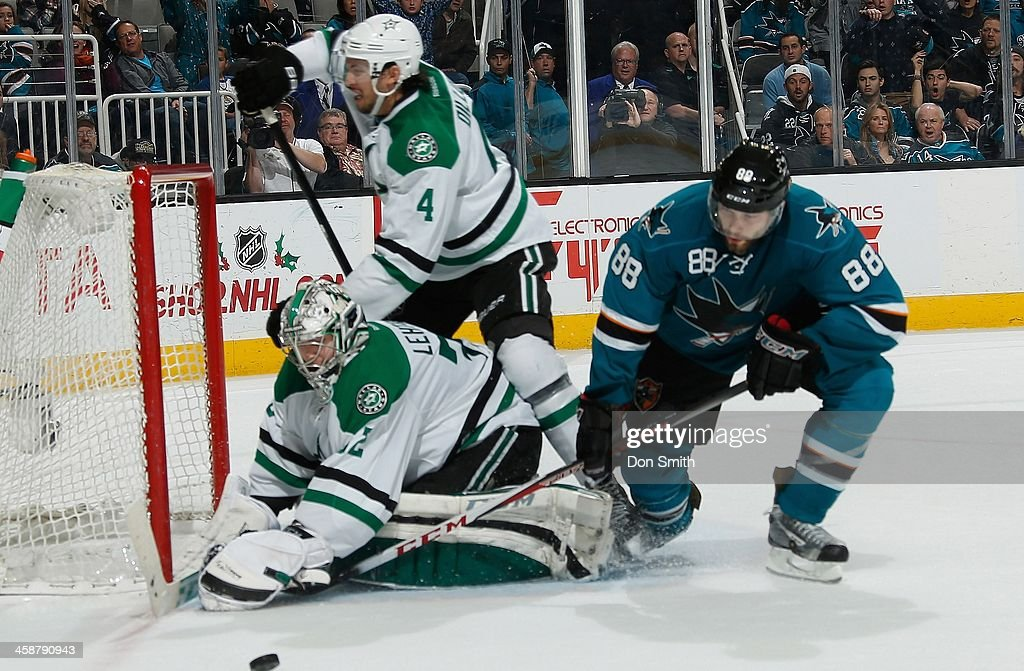Brent Burns #88 of the San Jose Sharks tries to get a shot into the net against Kari Lehtonen #32 and Brenden Dilon #4 of the Dallas Stars during an NHL game on December 21, 2013 at SAP Center in San Jose, California.