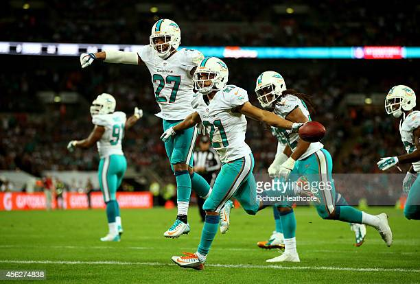 Brent Grimes of the Miami Dolphins celebrates with teammates after returning an interception for big yardage during the NFL match between the Oakland...