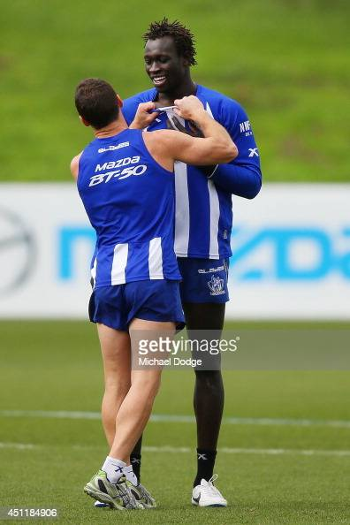Brent Harvey has a playful shove and shove with Majak Daw during a North Melbourne Kangaroos AFL training session at Arden Street Ground on June 25...