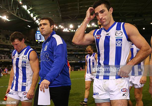 Brent Harvey of the Kangaroos and coach Brad Scott walk off after their defeat with Michael Firrito during the round 18 AFL match between the Carlton...