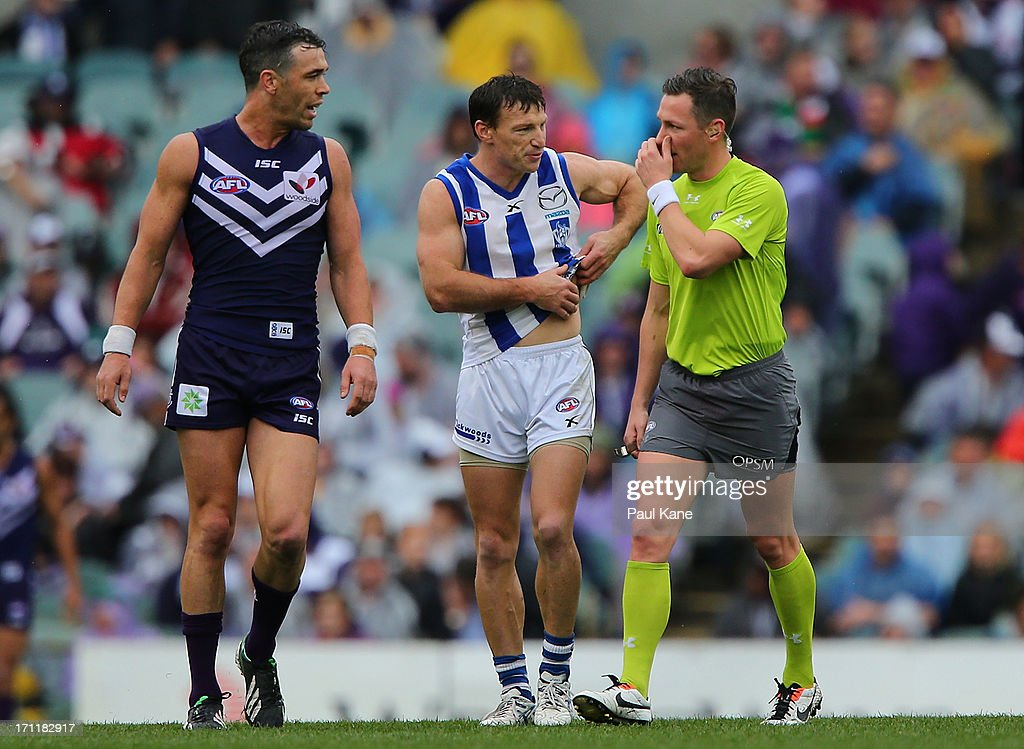 Brent Harvey of the Kangaroos talks to a field umpire with Ryan Crowley of the Dockers during the round 13 AFL match between the Fremantle Dockers and the North Melbourne Kangaroos at Patersons Stadium on June 23, 2013 in Perth, Australia.