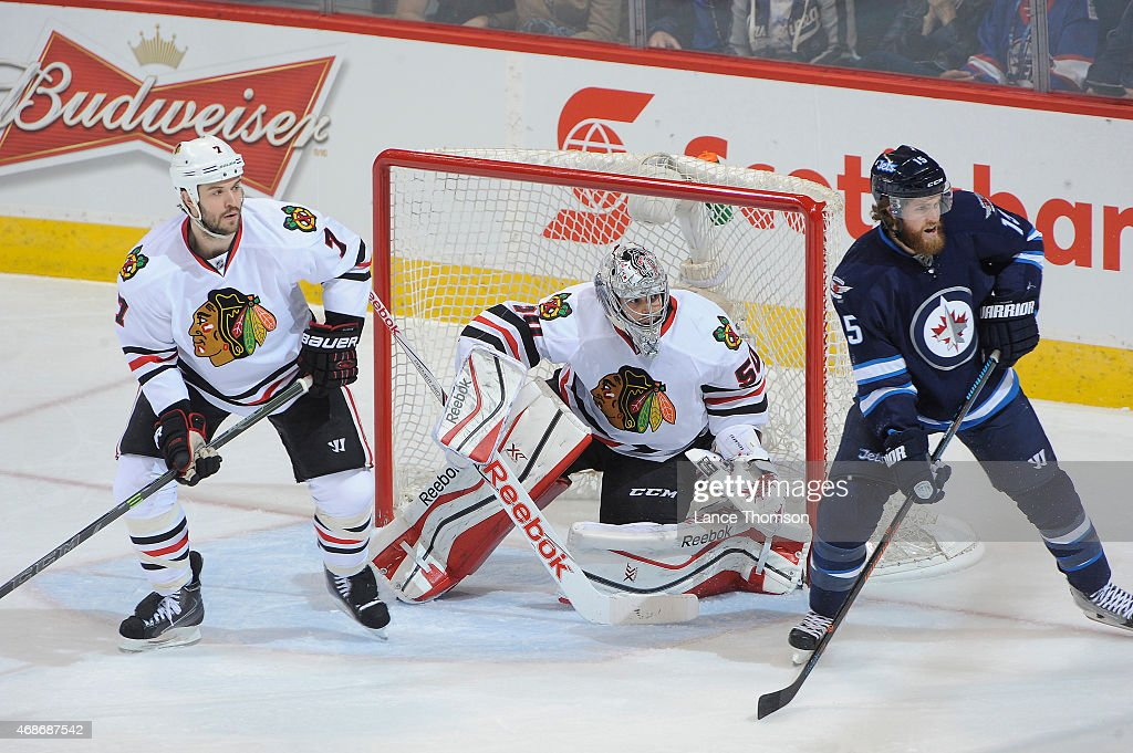 Brent Seabrook goaltender Corey Crawford of the Chicago Blackhawks and Matt Halischuk of the Winnipeg Jets keep an eye on the play along the boards...