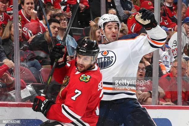 Brent Seabrook of the Chicago Blackhawks and Patrick Maroon of the Edmonton Oilers get physical by the boards in the third period at the United...