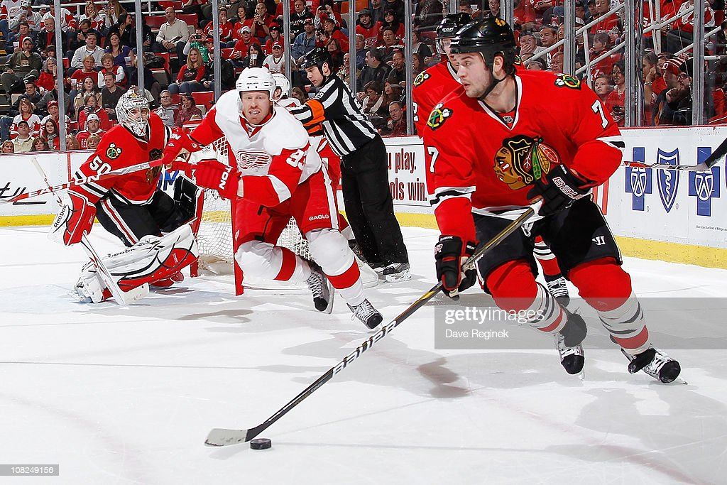 <a gi-track='captionPersonalityLinkClicked' href=/galleries/search?phrase=Brent+Seabrook&family=editorial&specificpeople=638862 ng-click='$event.stopPropagation()'>Brent Seabrook</a> #7 of the Chicago Blackhawks carries puck while <a gi-track='captionPersonalityLinkClicked' href=/galleries/search?phrase=Johan+Franzen&family=editorial&specificpeople=624356 ng-click='$event.stopPropagation()'>Johan Franzen</a> #93 of the Detroit Red Wings pursues during an NHL game at Joe Louis Arena on January 22, 2011 in Detroit, Michigan.