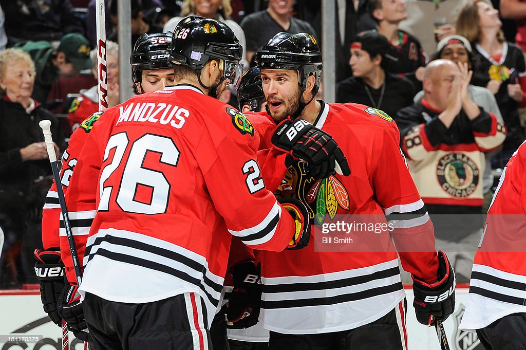 Brent Seabrook #7 of the Chicago Blackhawks celebrates with teammate Michal Handzus #26 after Handzus scored against the New York Islanders in the second period during the NHL game on October 11, 2013 at the United Center in Chicago, Illinois.