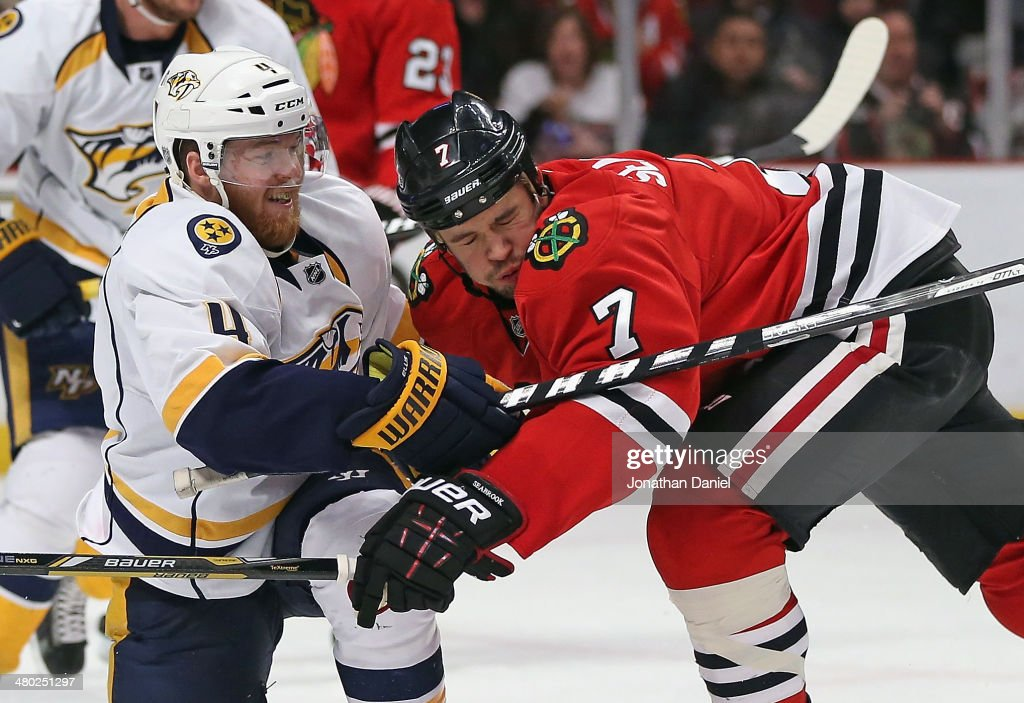 Brent Seabrook #7 of the Chicago Blackhawks collides with Ryan Ellis #4 of the Nashville Predators at the United Center on March 23, 2014 in Chicago, Illinois. The Predators defeated the Blackhawks 2-0.