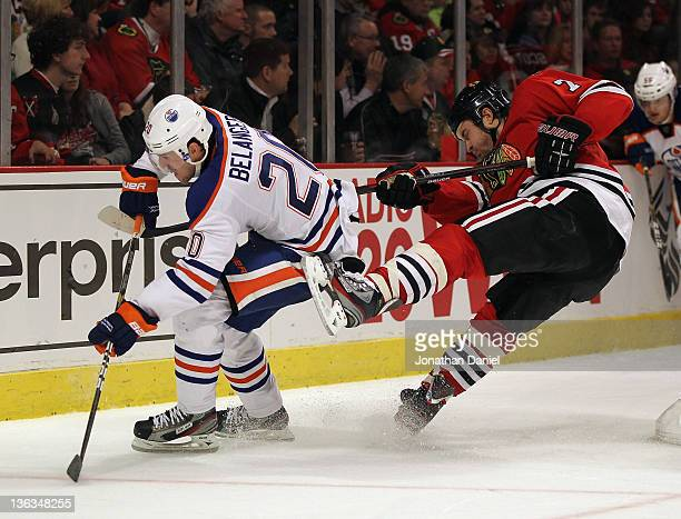 Brent Seabrook of the Chicago Blackhawks falls after colliding with Eric Belanger of the Edmonton Oilers at the United Center on January 2 2012 in...