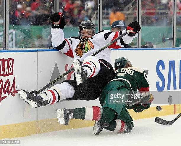 Brent Seabrook of the Chicago Blackhawks gets tripped up as Mikael Granlund of the Minnesota Wild pursues the puck during the first period at the TCF...