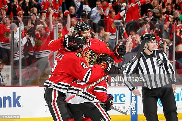 Brent Seabrook of the Chicago Blackhawks hugs Duncan Keith and Patrick Kane after scoring the game winning goal in the third overtime against the...