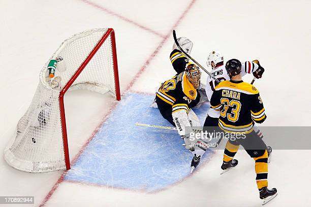 Brent Seabrook of the Chicago Blackhawks scores a game winning goal against Tuukka Rask of the Boston Bruins in overtime as Jonathan Toews and Zdeno...