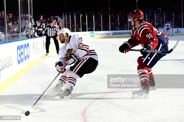 Brent Seabrook of the Chicago Blackhawks sends the puck back into the zone as Marcus Johansson of the Washington Capitals defends during the first...