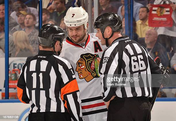 Brent Seabrook of the Chicago Blackhawks talks with referee Kelly Sutherland and linesman Darren Gibbs in an NHL game against the St Louis Blues on...