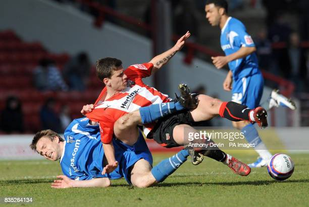Brentford's Charlie MacDonald is tackled by Gillingham's Mark Bentley during the CocaCola League Two match at Griffin Park Brentford