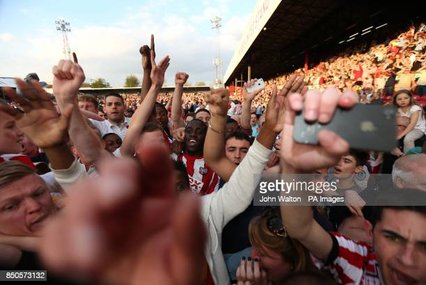 Brentford's Clayton Donaldson celebrates while being mobbed by fans after the final whistle