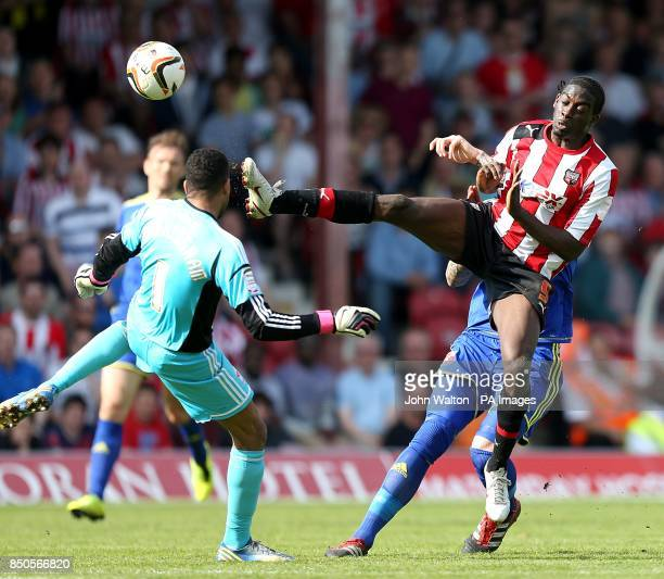 Brentford's Clayton Donaldson goes for the ball ahead of Swindon Town goalkeeper Wes Foderingham