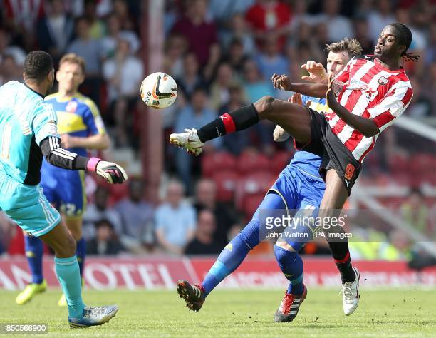 Brentford's Clayton Donaldson goes for the ball ahead of Swindon Town's Adam Forshaw and goalkeeper Wes Foderingham