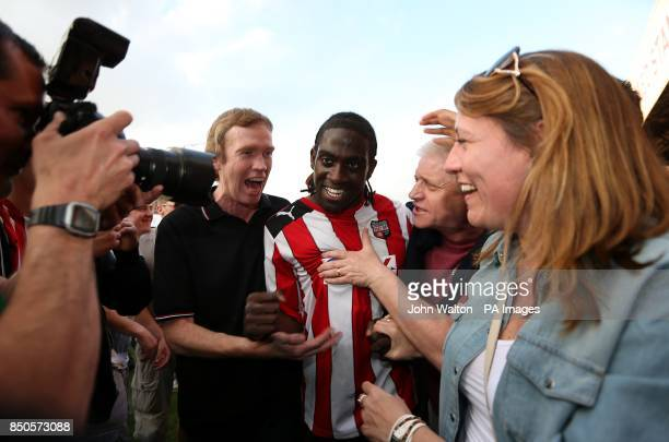 Brentford's Clayton Donaldson is mobbed by fans after the final whistle