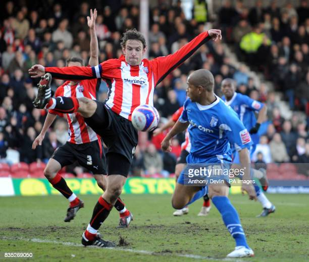 Brentford's Mark Phillips defends from Gillingham's Simeon Jackson during the CocaCola League Two match at Griffin Park Brentford