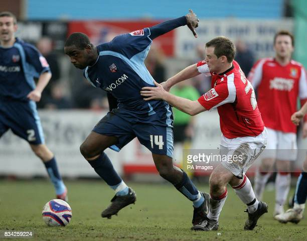 Brentford's Nathan Elder and Morecambe's Henry McStay in action during the CocaCola League Two match at Christie Park Morecambe