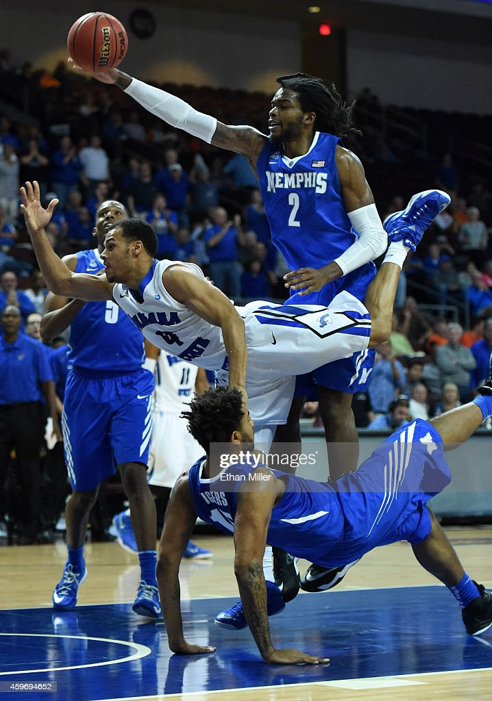 Brenton Scott of the Indiana State Sycamores is fouled as he drives to the basket by Kedren Johnson of the Memphis Tigers as Shaq Goodwin of the...