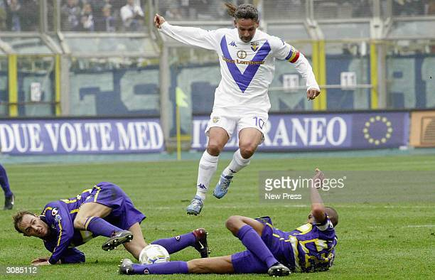 Brescia's Roberto Baggio avoids tackles from two Parma players during the Serie A match between Parma and Brescia on March 14 2004 in Parma Italy
