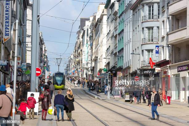 tram and pedestrians in the street 'rue Jean Jaures' in downtown Brest Passersby tram and buildings along the shopping street