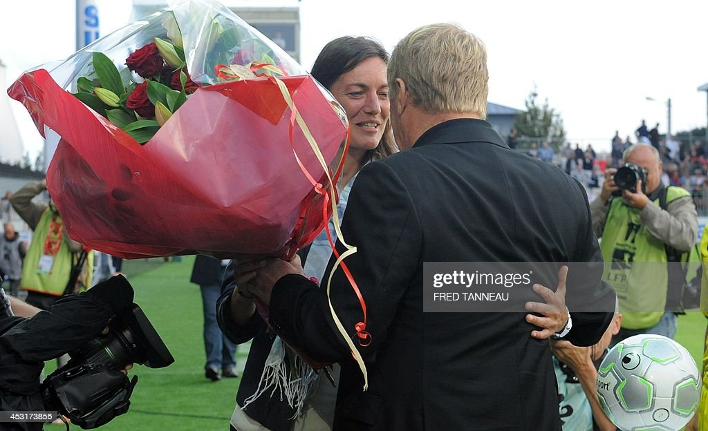 Brest's French coach Alex Dupont (R) offers flowers for her birthday to Clermont-Ferrand's French coach Corinne Diacre prior to the French L2 football match between Brest and Clermont-Ferrand on August 4, 2014 at the Francis Le Ble stadium in Brest, western France. Diacre is the first woman to lead a men's professional team in a major European country. Diacre was hired after Clermont's original choice, another woman, Portuguese Helena Costa, resigned abruptly the day before taking charge of the team.