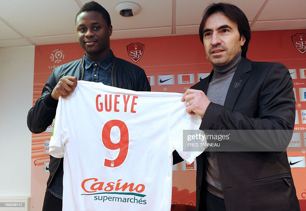 Brest's newly-recruited Senegalese forward Magaye Gueye (L) poses with his new jersey beside Brest's sport manager Corentin Martins on February 2, 2013 at the Francis Le Ble stadium in Brest, western France. Everton's forward Gueye, 22, was loaned to Brest L1 football club for six months, with purchase option, the club announced on February 1. AFP PHOTO / FRED TANNEAU