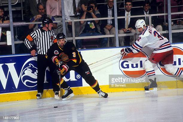 Bret Hedican of the Vancouver Canucks skates with the puck as Stephane Matteau of the New York Rangers tries to hook him as referee Terry Gregson...