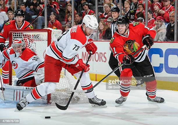 Brett Bellemore of the Carolina Hurricanes and Jeremy Morin of the Chicago Blackhawks battle for the puck during the NHL game on March 21 2014 at the...