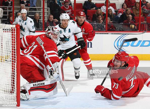 Brett Bellemore of the Carolina Hurricanes goes down in front of the net as Anton Khudobin deflects the puck wide during their NHL game against the...