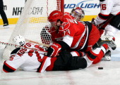 Brett Bellemore of the Carolina Hurricanes knocks Tom Kostopoulos of the New Jersey Devils away from the puck and clear of the crease during their...