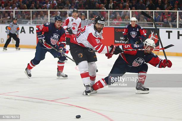 Brett Burns of Canada has his shot blocked by Jason Desantis of the United States of America during the 2015 Ice Hockey Classic match between the...