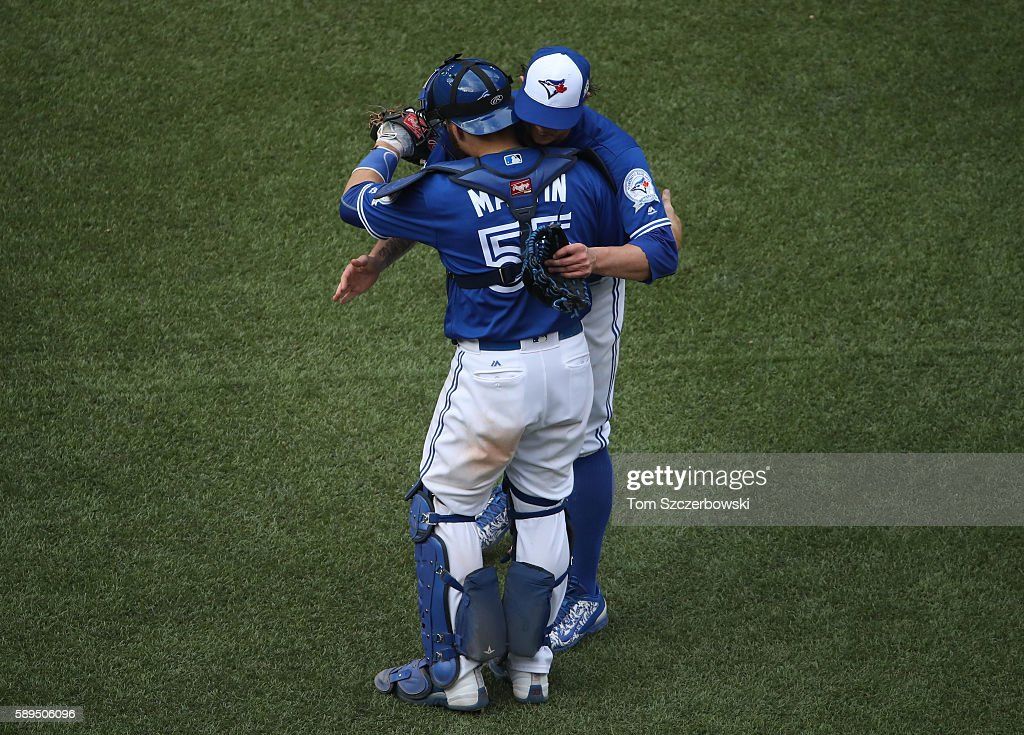 Brett Cecil #27 of the Toronto Blue Jays celebrates their victory with Russell Martin #55 during MLB game action against the Houston Astros on August 14, 2016 at Rogers Centre in Toronto, Ontario, Canada.