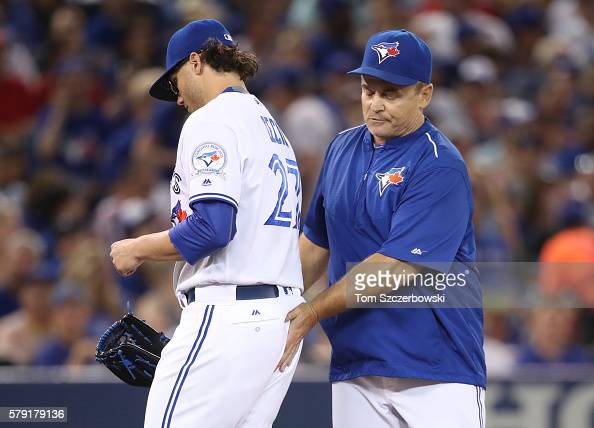 Brett Cecil of the Toronto Blue Jays exits the game as he is relieved by manager John Gibbons in the seventh inning during MLB game action against...