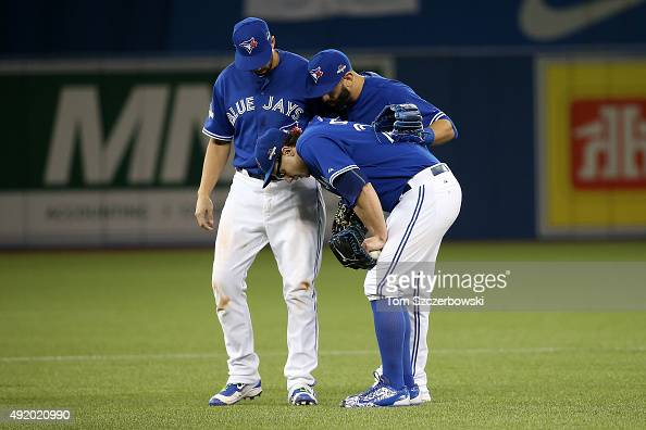 Brett Cecil of the Toronto Blue Jays is helped by teammates after a tag out to end the top of the eighth inning against the Texas Rangers during game...