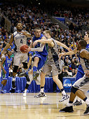 Brett Comer of the Florida Gulf Coast Eagles looks to pass the ball in the second half as he drives against Nate Lubick and D'Vauntes SmithRivera of...