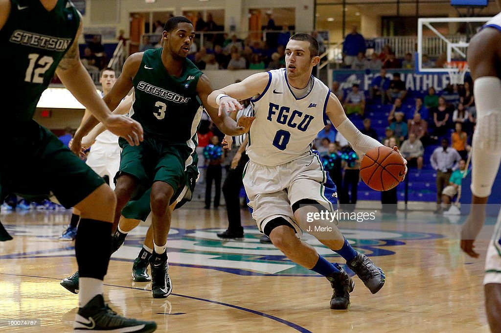Brett Comer #0 of the Florida Gulf Coast University Eagles advances the ball as <a gi-track='captionPersonalityLinkClicked' href=/galleries/search?phrase=Willie+Green&family=editorial&specificpeople=201653 ng-click='$event.stopPropagation()'>Willie Green</a> #3 of the Stetson Hatters defends during the game at Alico Arena on January 25, 2013 in Ft. Myers, Florida.