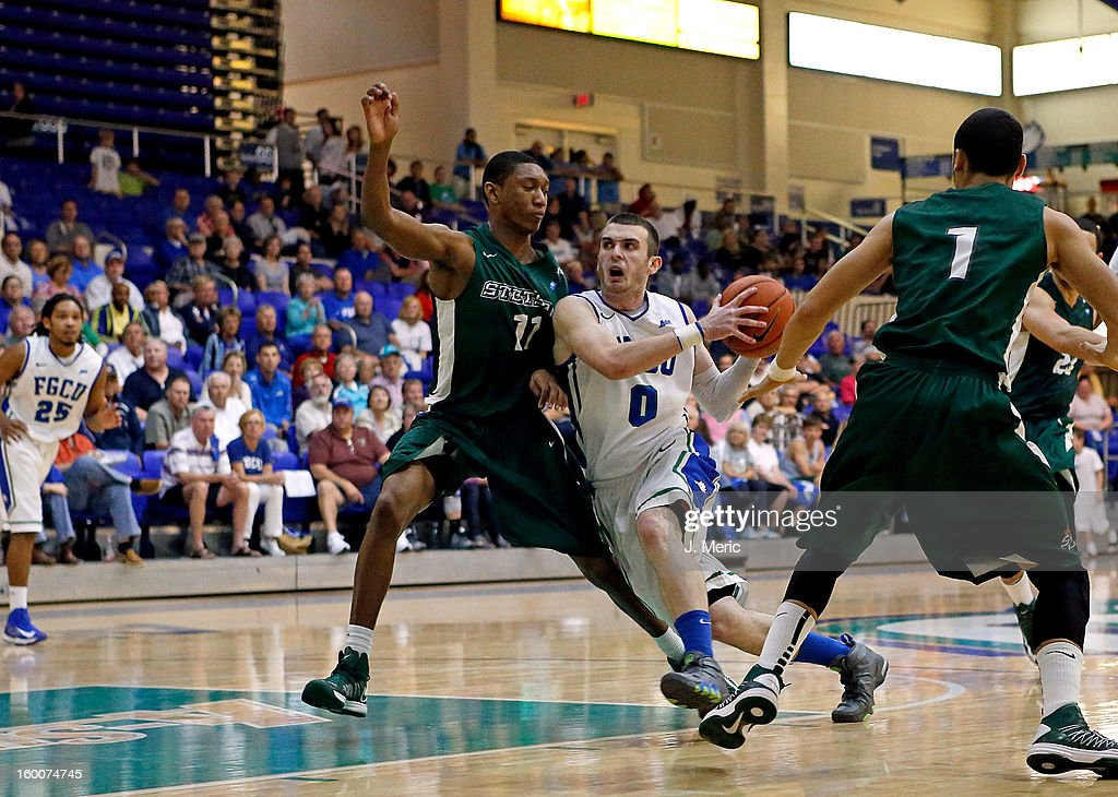 Brett Comer #0 of the Florida Gulf Coast University Eagles drives as Aaron Graham #11 of the Stetson Hatters defends during the game at Alico Arena on January 25, 2013 in Ft. Myers, Florida.