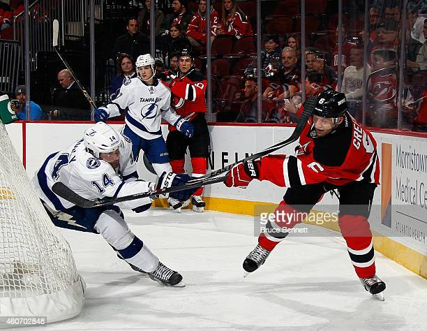 Brett Connolly of the Tampa Bay Lightning gets the stick up on Andy Greene of the New Jersey Devils at the Prudential Center on December 19 2014 in...