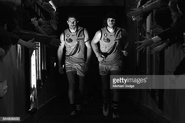 Brett Deledio of the Tigers and Trent Cotchin lead the team out at half time during the round 10 AFL match between the Essendon Bombers and the...